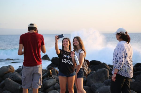 Adolescent girls taking a picture on Galapagos Islands' shore.