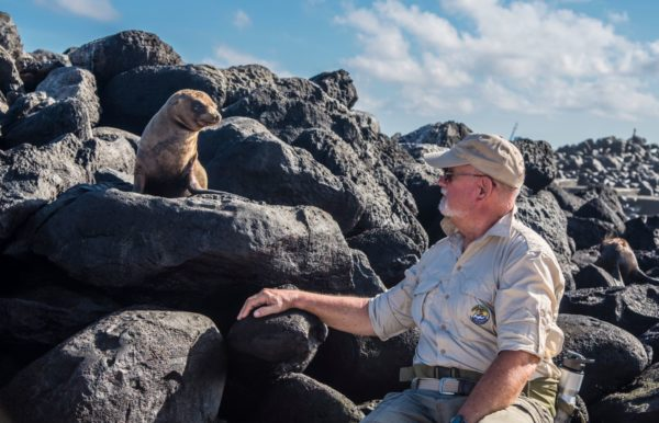 Man getting a close look at a sea lion pup.