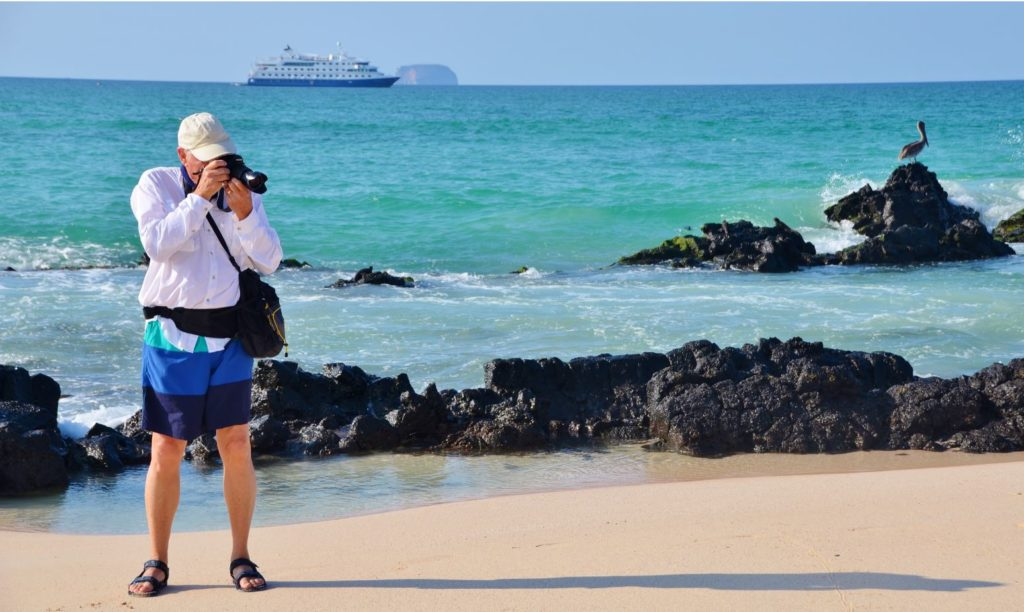 Tourist photographing at the shore of the Galapagos Islands.