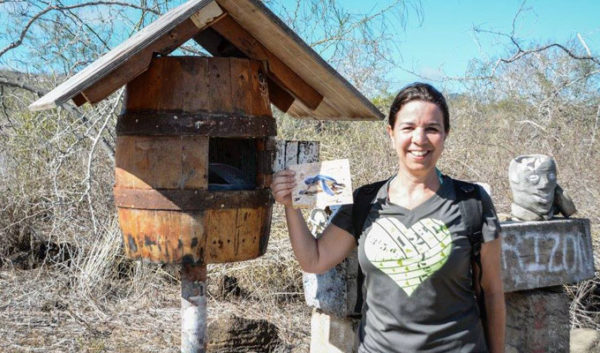 Guest with a post card at the Galapagos Post Office