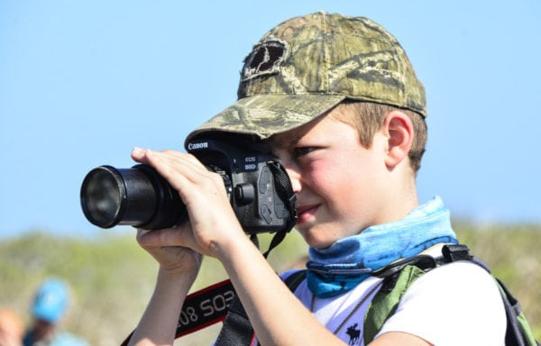 Kid taking a photo while and excursion in Galapagos.