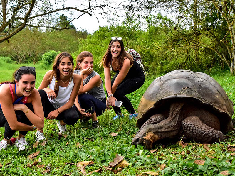 Santa Cruz II's guests with a Galapagos giant tortoise.