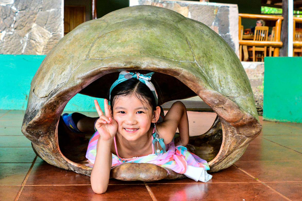 A happy kid inside a Galapagos giant tortoise shell